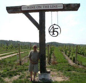 Me leaning on vineyard marker at 45 North Vineyard and Winery near Suttons Bay.